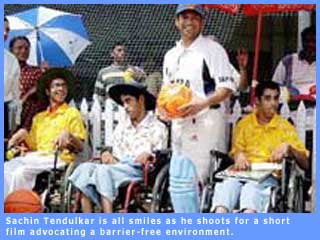 Picture of Sachin Tendulkar sharing a joke with children with disabilities.